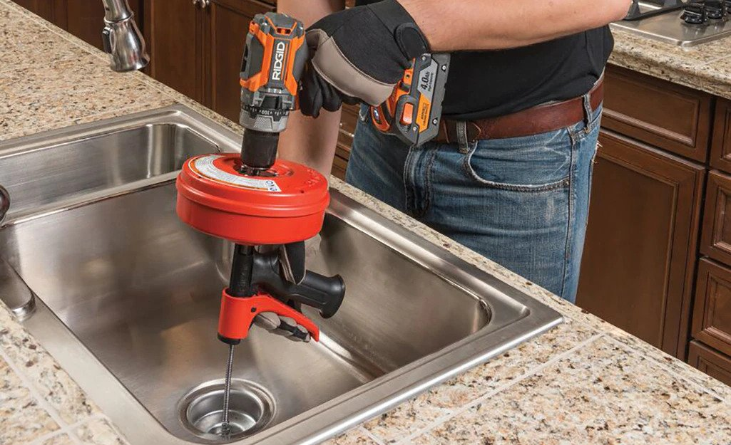 Clearing a clogged kitchen sink with a plumber's snake.
